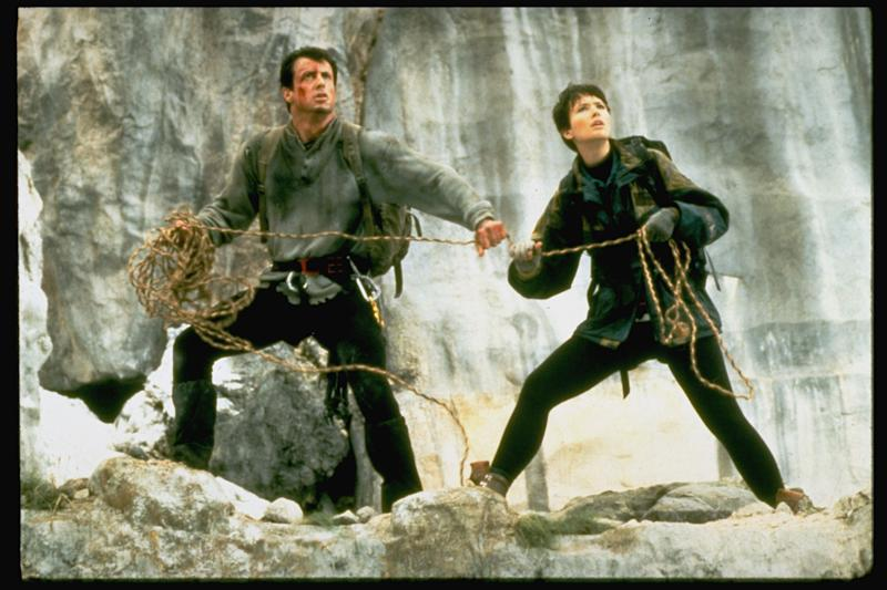 (L-R) Actors Sylvester Stallone & Janine Turner holding rope while standing on mountain ledge in scene fr. action thriller Cliffhanger. (Photo by John Bryson/The LIFE Images Collection/Getty Images)