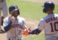 Houston Astros' Jose Altuve (27) is congratulated by teammate Yuli Gurriel (10) after scoring on a sacrifice fly against the Minnesota Twins in the first inning of a baseball game, Sunday, June 13, 2021, in Minneapolis. (AP Photo/Andy Clayton-King)