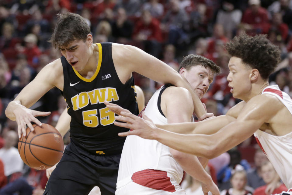 Iowa's Luka Garza (55) tries to control the ball against the defense of Nebraska's Tanner Borchardt, center, and Isaiah Roby, right, during the first half of an NCAA college basketball game in Lincoln, Neb., Sunday, March 10, 2019. (AP Photo/Nati Harnik)