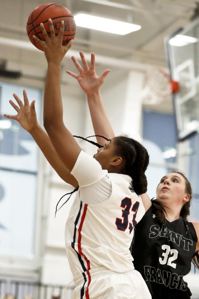 Robert Morris' Nneka Ezeigbo (33) shoots as St. Francis (Pa)'s Courtney Zezza (32) defends during the first half of an NCAA college basketball game for the championship of the Northeast Conference women's tournament, Sunday, March 17, 2019, in Moon, Pa. (AP Photo/Keith Srakocic)