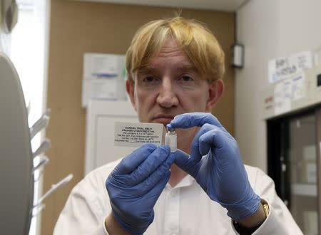 Professor Adrian Hill, Director of the Jenner Institute, and Chief Investigator of the trials, holds a phial containing the Ebola vaccine at the Oxford Vaccine Group Centre for Clinical Vaccinology and Tropical Medicine (CCVTM) in Oxford