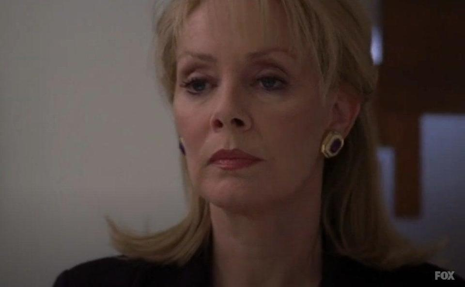 A woman(Jean Smart) in a formal outfit looking at something offscreen