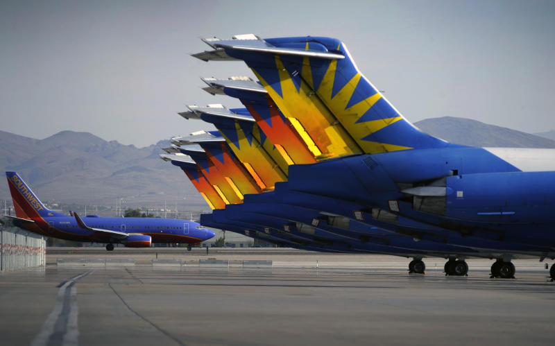 In this Thursday, May 9, 2013, photo, a Southwest airline taxis by parked Allegiant Air jetliners at McCarran International Airport in Las Vegas. While other U.S. airlines have struggled with the ups and downs of the economy and oil prices, tiny Allegiant Air has been profitable for 10 straight years. (AP Photo/David Becker)