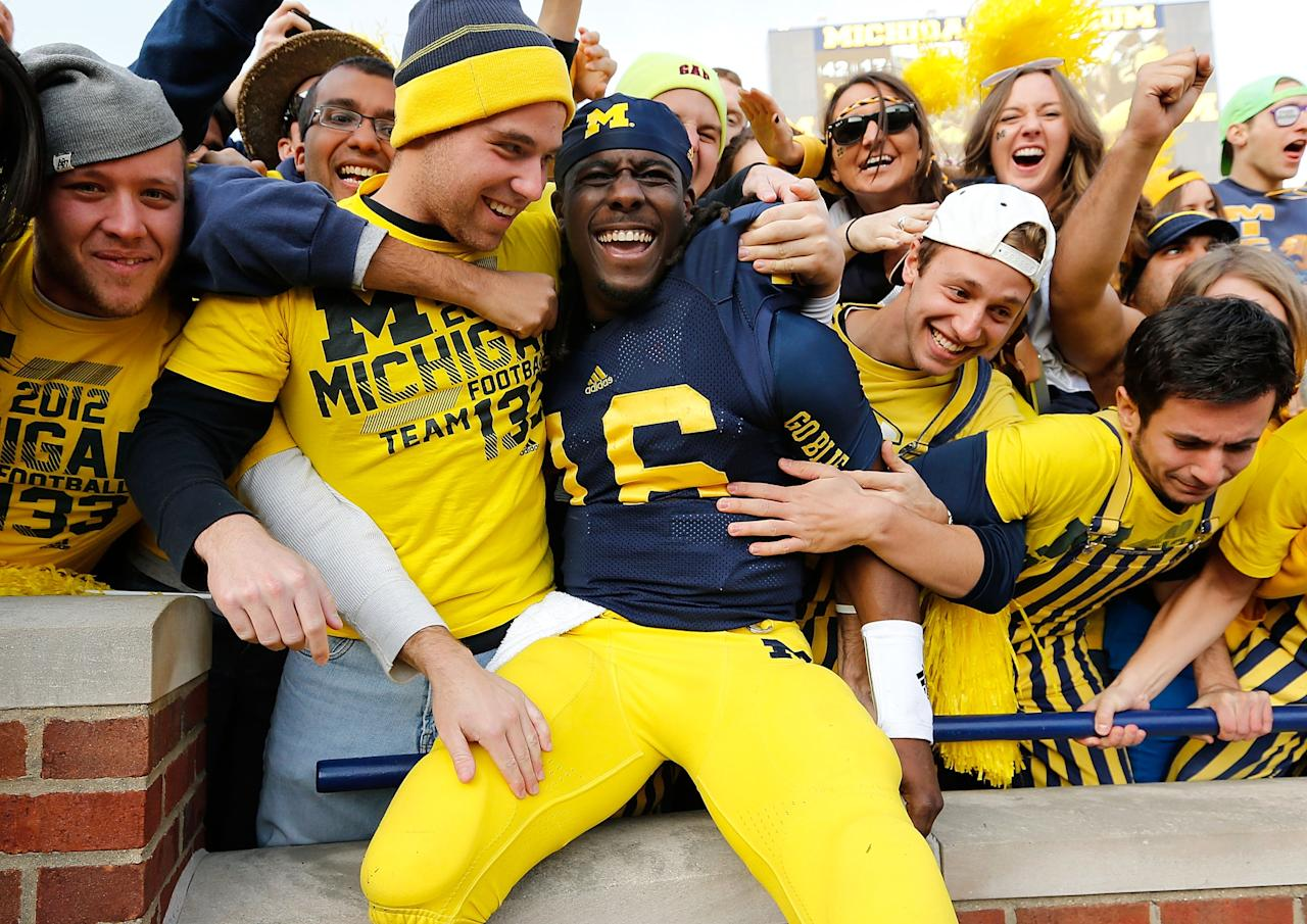 ANN ARBOR, MI - NOVEMBER 17:  Denard Robinson #16 of the Michigan Wolverines celebrates a 42-17 victory over the Iowa Hawkeyes with fans at Michigan Stadium on November 17, 2012 in Ann Arbor, Michigan. (Photo by Gregory Shamus/Getty Images)