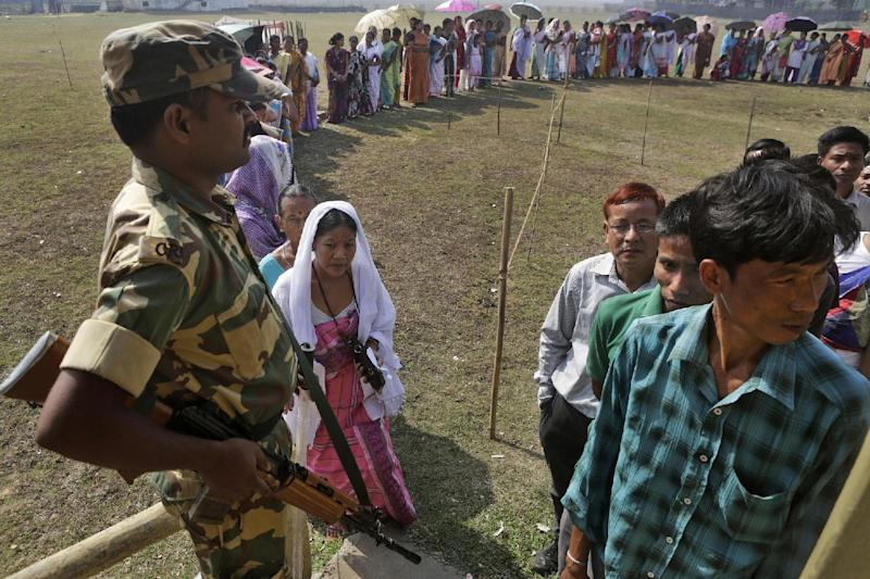 A security person stands guard as Indians wait in a queue to cast their votes during the sixth phase of polling of the Indian parliamentary elections in Sonapur village, outskirts of Gauhati, India, Thursday, April 24, 2014.The multiphase voting across the country runs until May 12, with results for the 543-seat lower house of parliament expected on May 16. (AP Photo/Anupam Nath)