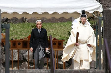 FILE PHOTO: Japan's Emperor Akihito is led by a Shinto priest after visiting the tomb of his late father Hirohito to report his abdication at the Musashino Imperial Mausoleum in Tokyo, Japan April 23, 2019.  Koji Sasahara/Pool via REUTERS