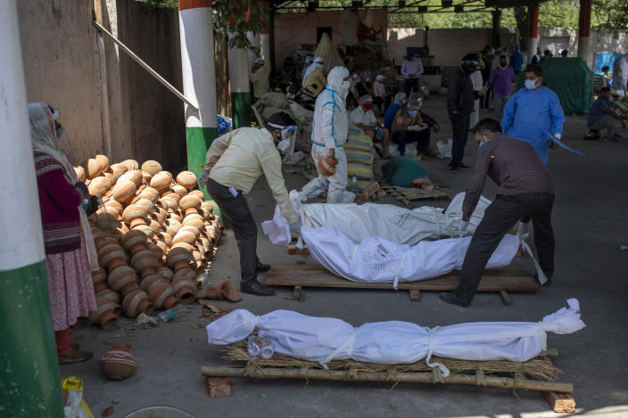 People line up dead bodies of those who died of COVID-19 at a crematorium, in New Delhi, India, Saturday, April 24, 2021. Delhi has been cremating so many bodies of coronavirus victims that authorities are getting requests to start cutting down trees in city parks, as a second record surge has brought India's tattered healthcare system to its knees. (AP Photo/Altaf Qadri)