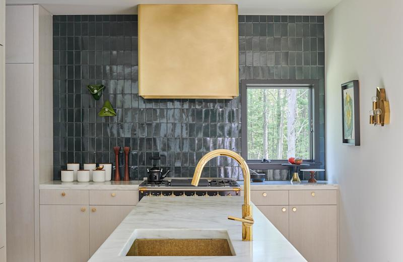 In the Salisbury, Connecticut, kitchen of architects David Fox and Christopher Stone (cofounders of the firm Stonefox), surfaces of Imperial Danby marble complement Waterworks tile features; the brass hood was custom-designed and the range is by Lacanche.