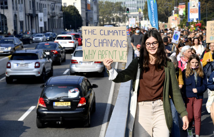 A girl holds up a sign to oncoming traffic as she participates in a climate march and demonstration in Brussels, Sunday, Oct. 10, 2021. Some 80 organizations are joining in a climate march through Brussels to demand change and push politicians to effective action in Glasgow later this month.(AP Photo/Geert Vanden Wijngaert)
