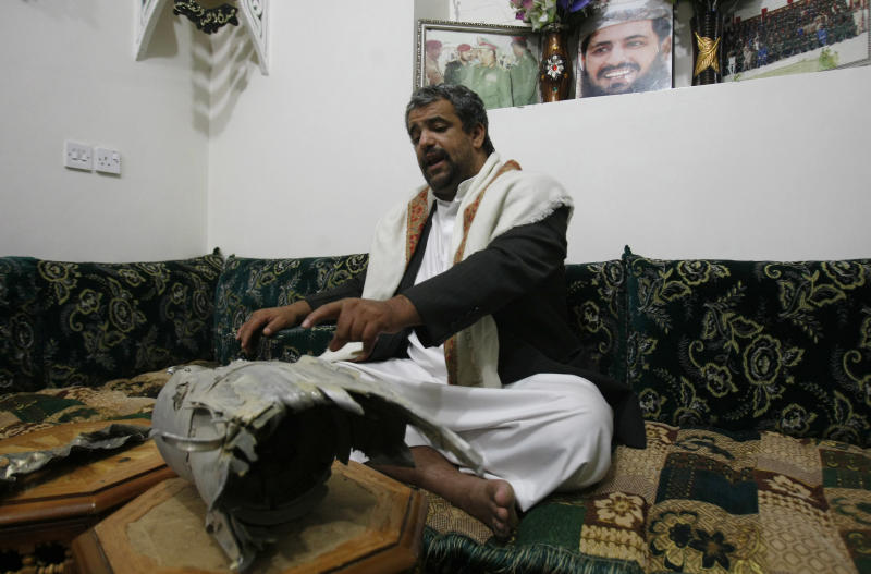 In this photo taken on Tuesday, Feb. 11, 2014, Himyar al-Qadhy, whose brother Adnan, was killed in 2012 by U.S drone strike east of Sanaa, Yemen, points to what he says is the rocket that killed his brother, a Yemeni army brigadier suspected of involvement in a militant attack in 2008 against the US Embassy in Sanaa. The brother denies that Adnan was a member of the al-Qaida. The portrait on the wall shows his late brother. (AP Photo/Hani Mohammed)