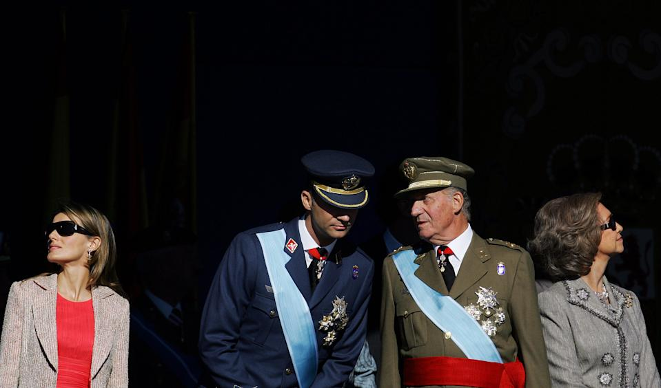 Spanish Crown Prince Felipe (2nd L) and King Juan Carlos talk as Princess Letizia (L) and Queen Sofia (R) watch a military parade during Spain's National Day in Madrid October 12, 2006. REUTERS/Susana Vera  (SPAIN)