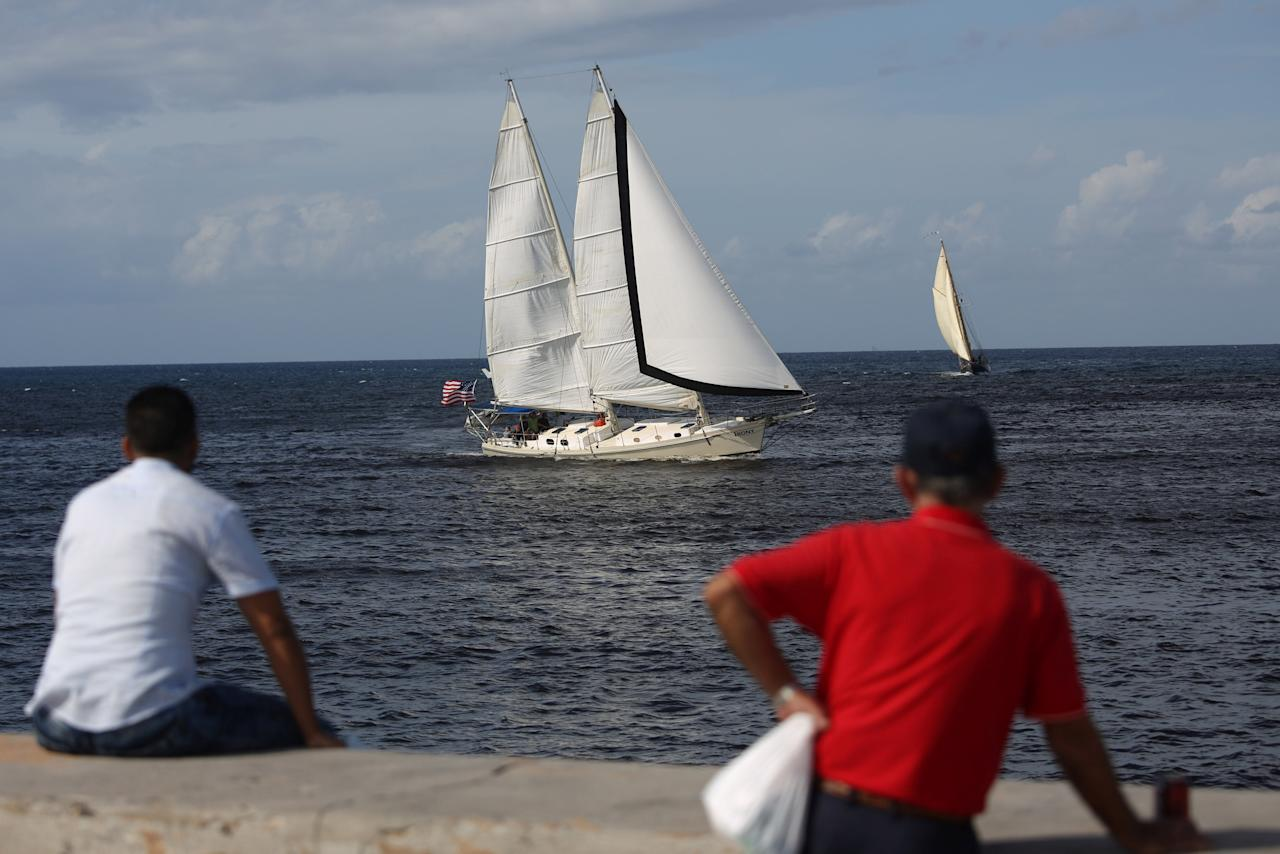 People look at the U.S. Irony sailing boat passing nearby during a race between Havana and Cayo Hueso in the U.S., in Havana, Cuba, February 2, 2017. REUTERS/Alexandre Meneghini