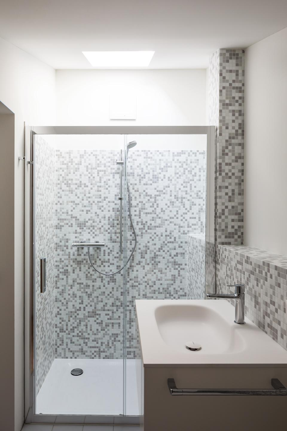 Bathroom renovated with mosaic of grey tiles. Washbasin, shower and skylight. No one inside