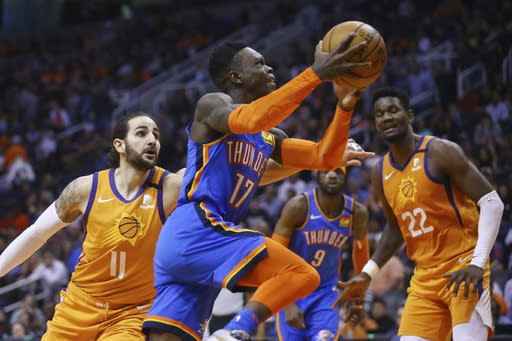 FILE - Oklahoma City Thunder guard Dennis Schroder (17) drives past Phoenix Suns guard Ricky Rubio (11) as Suns center Deandre Ayton (22) and Thunder center Nerlens Noel (9) watch during the first half of an NBA basketball game in Phoenix, in this Friday, Jan. 31, 2020, file photo. Teams may begin making trades Monday, according to a memo sent to teams and obtained early Sunday, Nov. 15, 2020, by The Associated Press. And the first deal known to be tentatively agreed upon would send guard Dennis Schrder from Oklahoma City to the champion Los Angeles Lakers for Danny Green and the No. 28 pick in Wednesdays draft, a person with knowledge of that agreement told the AP. (AP Photo/Ross D. Franklin, File)