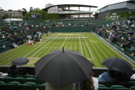 Spectators wait with umbrellas as play is interrupted because of rain during the women's doubles quarterfinals match on day nine of the Wimbledon Tennis Championships in London, Wednesday, July 7, 2021. (AP Photo/Kirsty Wigglesworth)