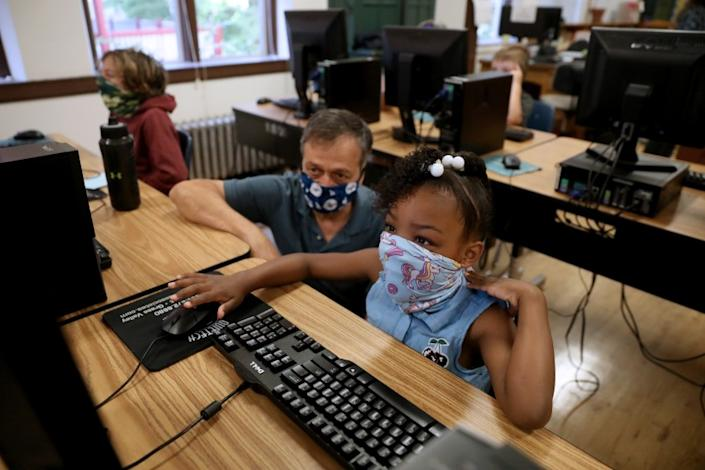"China Arkansas, 8, an incoming third-grader at Mount St. Mary's Academy in Grass Valley, Calif., takes an assessment test under the watch of teacher David Pistone. <span class=""copyright"">(Gary Coronado / Los Angeles Times)</span>"