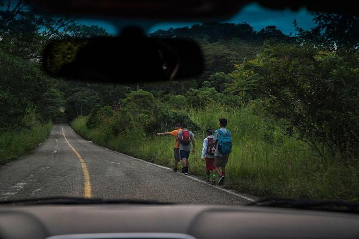 "Migrants walk along a highway near Palenque, Chiapas, on Oct. 21. The highway is known by locals as ""El Gran Corredor del Pacífico del Migrante,"" or ""The Great Pacific Corridor of the Migrant."