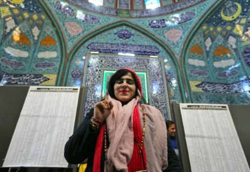 An Iranian woman displays her ink-stained finger after voting during parliamentary election at a polling station in Tehran