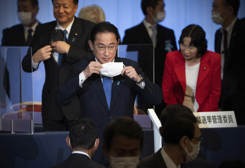Japan's former Foreign Minister Fumio Kishida, center, puts on his face mask as he leaves the stage after winning the Liberal Democrat Party leadership election in Tokyo Wednesday, Sept. 29, 2021. Kishida won the governing party leadership election on Wednesday and is set to become the next prime minister, facing the imminent task of addressing a pandemic-hit economy and ensuring a strong alliance with Washington to counter growing regional security risks. (Carl Court/Pool Photo via AP)