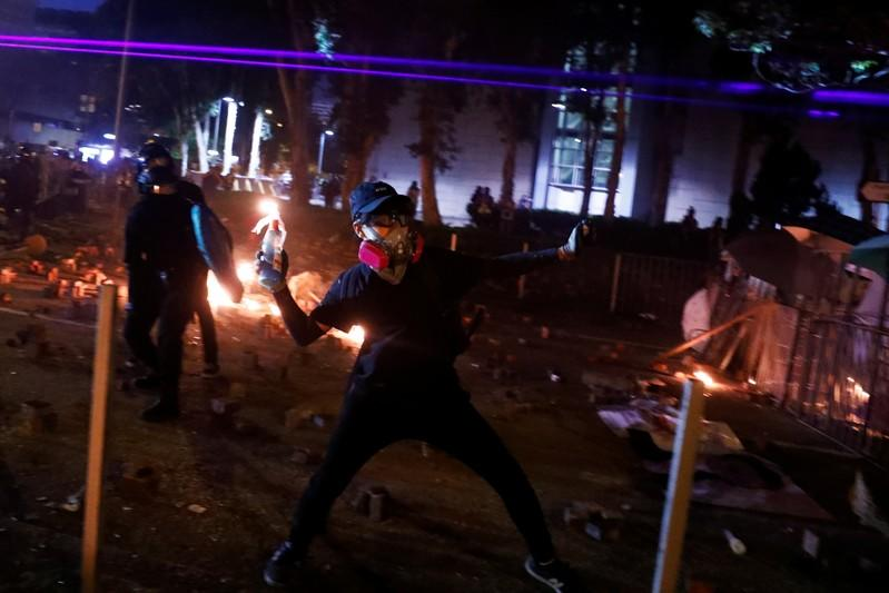 An anti-government protester throws a Molotov cocktail during clashes with the police outside the Polytechnic University in Hong Kong