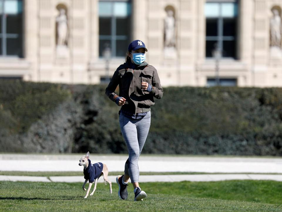 A jogger with her dog in the Tuileries Garden in Paris amid the coronavirus lockdown in France, 23 March, 2020: Reuters
