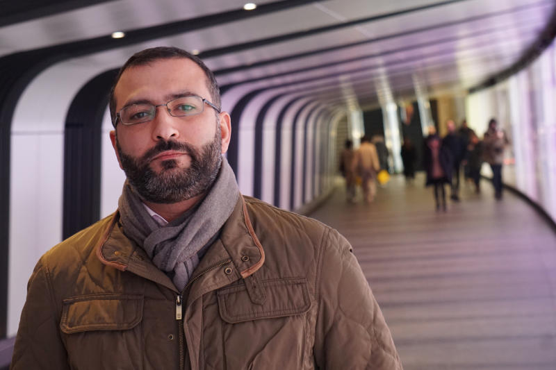 Mazen Masri, an academic and a consultant to the legal team suing the NSO Group in Israel over alleged abuses involving its spyware, poses for a photograph in a pedestrian underpass leading to King's Cross Station in London on Monday, Jan. 27, 2019. He is among half a dozen people who have been approached by undercover operatives on false pretexts over the past two months. All six have crossed paths with the NSO Group in some way. (AP Photo/Raphael Satter)