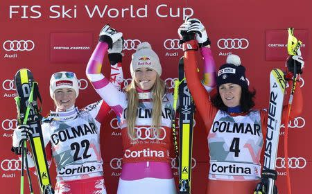 Lindsey Vonn of the U.S. (C) celebrates on the podium with second placed Elisabeth Goergl of Austria (L) and third placed Daniela Meringhetti of Italy after winning the women's World Cup Downhill skiing race in Cortina D'Ampezzo January 18, 2015.   REUTERS/Stringer