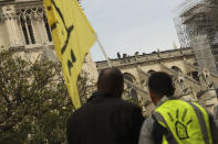Protesters look at technicians working on top of the Notre Dame cathedral in Paris, Monday, April 22, 2019. In the wake of the fire last week that gutted Notre Dame, questions are being raised about the state of thousands of other cathedrals, palaces and village spires that have turned France — as well as Italy, Britain and Spain — into open air museums of Western civilization. (AP Photo/Francisco Seco)