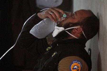 A civil defence member breathes through an oxygen mask, after what rescue workers described as a suspected gas attack in the town of Khan Sheikhoun in rebel-held Idlib