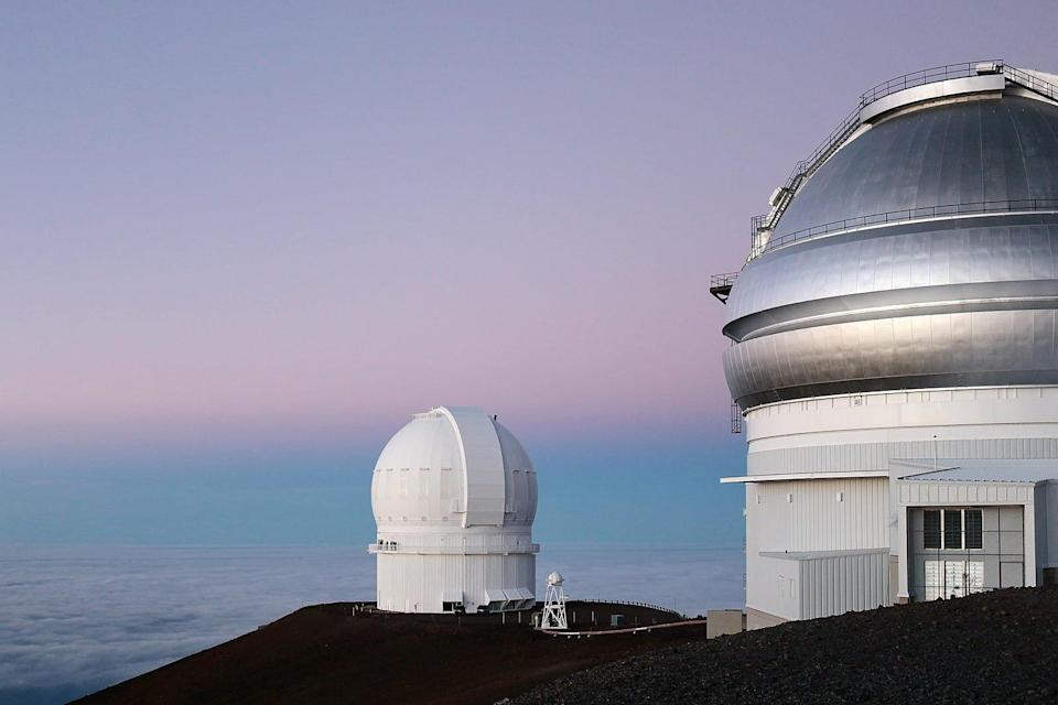 Two telescopes in Hawaii look at a bluish-pink sky, snapping a large-scale view of the solar system.