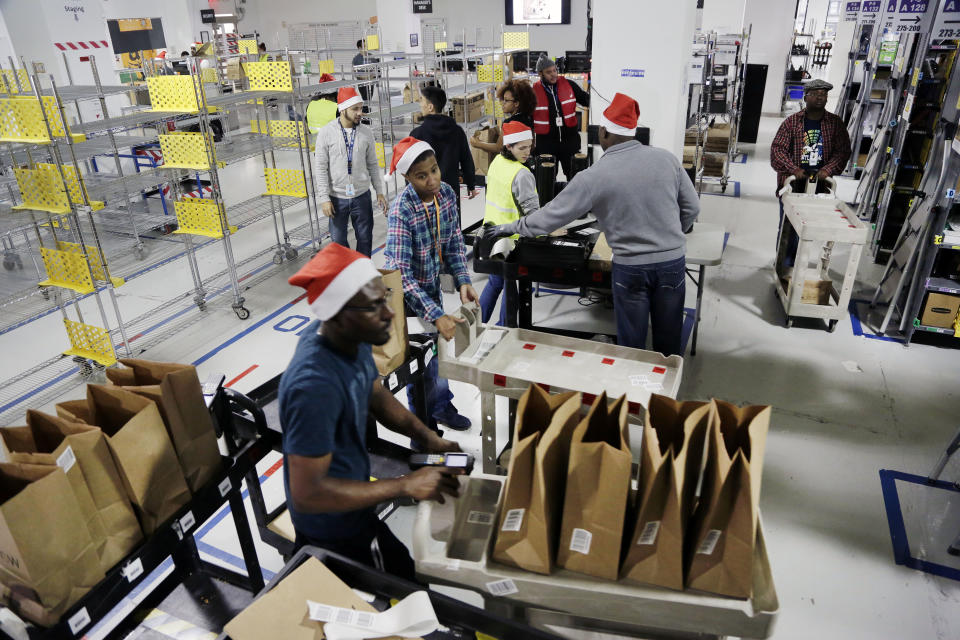 Amazon Prime employees push carts with bags loaded with goods for delivery (AP Photo/Mark Lennihan)