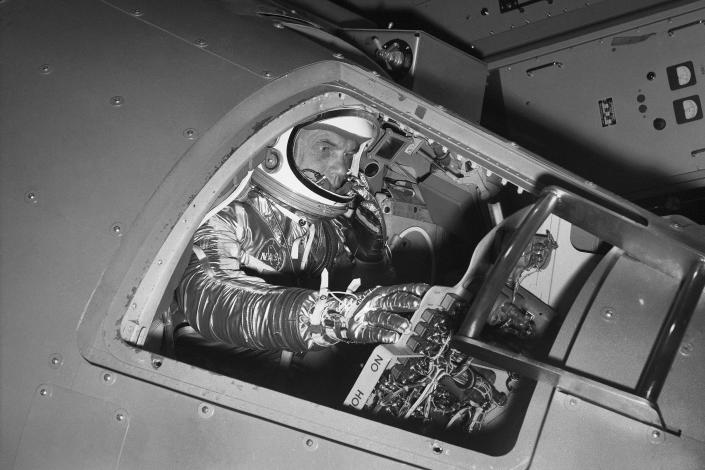 FILE - In this Jan. 11, 1961 file photo, Marine Lt. Col. John Glenn reaches for controls inside a Mercury capsule procedures trainer as he shows how the first U.S. astronaut will ride through space during a demonstration at the National Aeronautics and Space Administration Research Center in Langley Field, Va. In 2021, as more companies start selling tickets to space and the cosmos opens for travel like never before, a question looms above all others. Who gets to call themselves an astronaut? (AP Photo/File)
