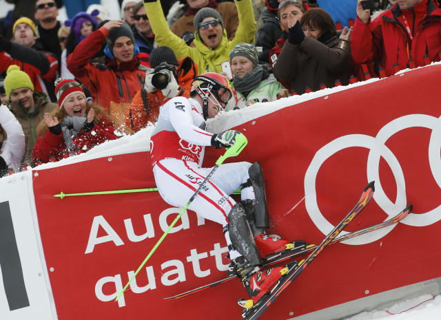 Winner Marcel Hirscher of Austria hits the protection fence as he finishes the second run of men's Slalom event of the Alpine Skiing World Cup downhill ski race in Kitzbuehel January 27, 2013. REUTERS/Leonhard Foeger (AUSTRIA - Tags: SPORT SKIING TPX IMAGES OF THE DAY) - RTR3D1A7