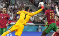 Portugal's Danilo Pereira, right, and France's goalkeeper Hugo Lloris collide as they compete for the ball during the Euro 2020 soccer championship group F match between Portugal and France at the Puskas Arena, Budapest, Hungary, Wednesday, June 23, 2021. (AP Photo/Darko Bandic,Pool)