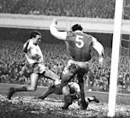 The ball has stuck in the mud and deceived Arsenal goalkeeper Kelsey, but centre-half Snedden is there in the nick of time to kick away from the onrushing Manchester United right half Nobby Stiles in the First Division match at Highbury, London. (Photo by PA Images via Getty Images)