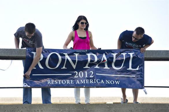 Matt Pierce, Vanessa Shunda, and Norm Shunda, all from Las Vegas, secure a banner to a walkway outside the venue for a Republican Presidential Debate in Ames, Iowa, August 11, 2011. (REUTERS/Daniel Acker)