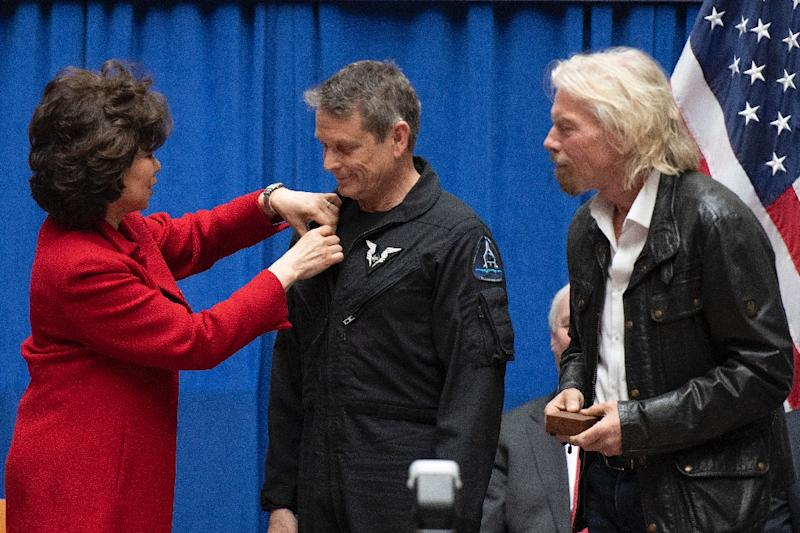 """US Transportation Secretary Elaine Chao (L) pins FAA commercial astronaut wings on test pilot Mark """"Forger"""" Stucky's during a ceremony at the Department of Transportation in Washington, on February 7, 2019 (AFP Photo/Jim WATSON)"""