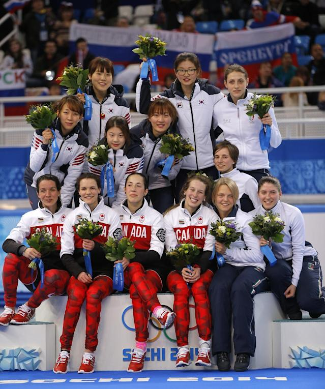 The South Korean team, top left, the Canadian team, front left, and the Italian team, top and bottom right, pose for photographers during the flower ceremony for the women's 3000m short track speedskating relay final at the Iceberg Skating Palace during the 2014 Winter Olympics, Tuesday, Feb. 18, 2014, in Sochi, Russia. South Korea placed first, followed by Canada and Italy. (AP Photo/Vadim Ghirda)