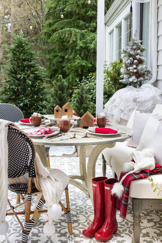 """<p>If it's warm enough, why not set a Christmas table outside? The wooden nesting houses from Joanna Gaines's <a href=""""https://www.countryliving.com/shopping/g22637799/joanna-gaines-bathroom-collection-hearth-and-hand-magnolia-target/"""" rel=""""nofollow noopener"""" target=""""_blank"""" data-ylk=""""slk:Hearth & Hand with Magnolia"""" class=""""link rapid-noclick-resp"""">Hearth & Hand with Magnolia</a> collection serves as a cute centerpiece, while hot chocolate and throws at each place keeps things cozy.</p><p><strong>Get the tutorial at <a href=""""https://www.zevyjoy.com/uncategorized/simple-outdoor-christmas-table-decorating-a-christmas-tablescape-tour/"""" rel=""""nofollow noopener"""" target=""""_blank"""" data-ylk=""""slk:Zevy Joy"""" class=""""link rapid-noclick-resp"""">Zevy Joy</a>.</strong></p><p><a href=""""https://www.target.com/p/wood-nesting-house-set-of-3-hearth-hand-153-with-magnolia/-/A-52591970?"""" rel=""""nofollow noopener"""" target=""""_blank"""" data-ylk=""""slk:SHOP WOODEN HOUSES"""" class=""""link rapid-noclick-resp"""">SHOP WOODEN HOUSES</a></p>"""