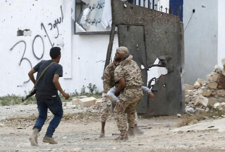 Fighters loyal to Libya's Government of National Accord carry a wounded man, as clashes rage south of the capital Tripoli