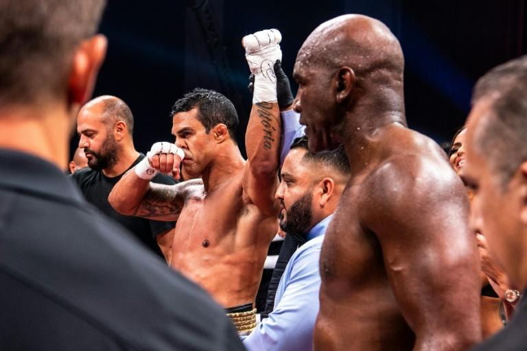 Brazilian martial artist Vitor Belfort (3rd L) celebrates after defeating US former professional boxer Evander Holyfield (2nd R) during a boxing fight at Hard Rock Live in Hollywood, Florida on September 11, 2021 (AFP/CHANDAN KHANNA)