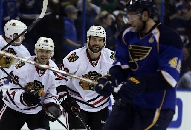 Chicago Blackhawks' Michal Handzus, of Slovakia, and teammate Brandon Bollig, center, celebrate as St. Louis Blues' David Backes, right, skates off the ice at the end of Game 5 of a first-round NHL hockey playoff series Friday, April 25, 2014, in St. Louis. The Blackhawks won 3-2 in overtime. (AP Photo/Jeff Roberson)
