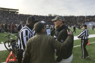 Harvard coach Tim Murphy, right, gets an updated as demonstrators stage a protest on the field at the Yale Bowl disrupting the start of the second half of an NCAA college football game between Harvard and Yale, Saturday, Nov. 23, 2019, in in New Haven, Conn. (AP Photo/Jimmy Golen)