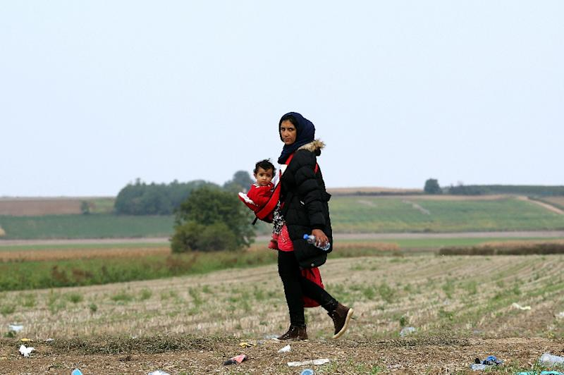 A woman carries a baby as migrants and asylum seekers walk through a field near the western Serbian town of Sid on September 24, 2015 (AFP Photo/)