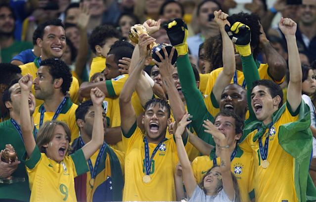 FILE - This Sunday, June 30, 2013 file photo shows Brazil's Neymar, center, as he lifts the trophy after winning the soccer Confederations Cup final between Brazil and Spain at the Maracana stadium in Rio de Janeiro, Brazil. (AP Photo/Victor Caivano, File)