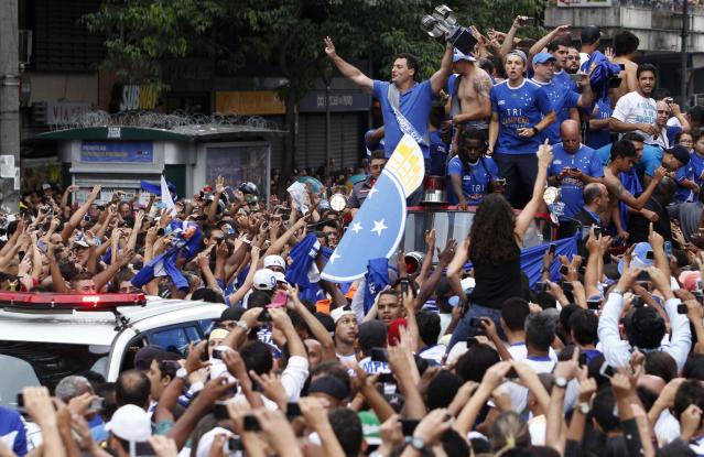 Cruzeiro's players celebrate with their fans after winning the Brazilian Serie A championship title in Belo Horizonte November 14, 2013. Cruzeiro were confirmed as Brazilian champions during half time of their 3-1 win over Vitoria on Wednesday when their closest rivals slipped up and helped ease their way to a third national title. There was still 45 minutes to go in their own game but closest challengers Atletico Paranaense went down 2-1 at Criciuma in an earlier match and Cruzeiro knew they could not be caught at the top. They still won the match with second half goals from Ricardo Goulart and Julio Baptista to end the game with a 16-point lead with four matches remaining. REUTERS/Washington Alves (BRAZIL - Tags: SPORT SOCCER)