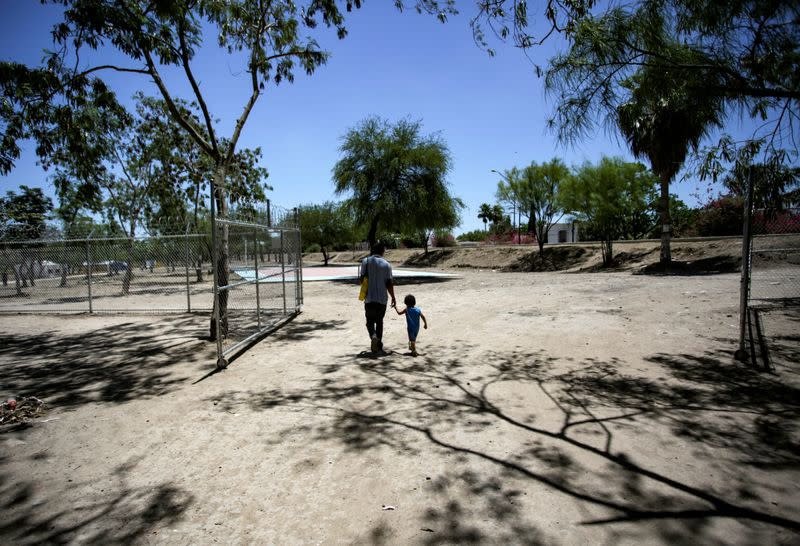 A migrant man hold his son's hand as they leave a migrant encampment during the outbreak of COVID-19 in Matamoros