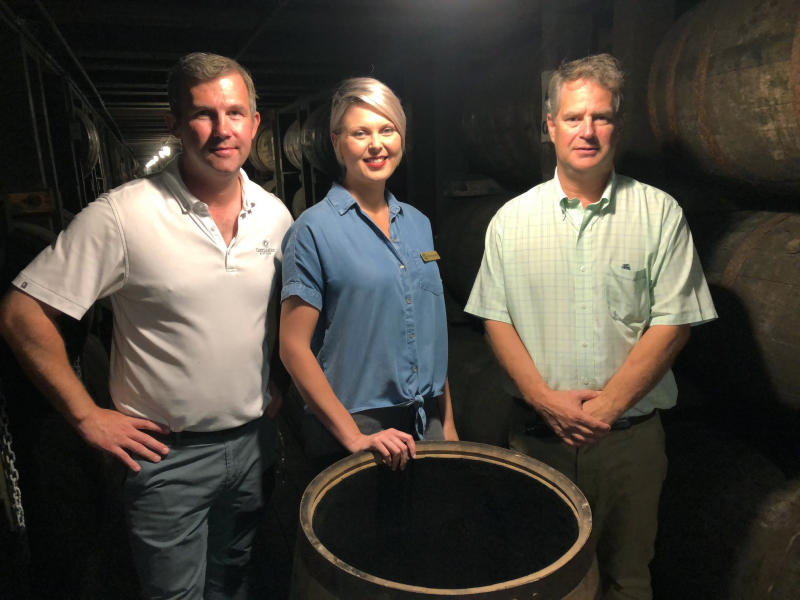 In this Friday, Sept. 14, 2018 photo, master distiller Marianne Eaves, center, is flanked by co-owners Will Arvin, right, and Wes Murray, while posing in a barrel warehouse Castle & Key Distillery in Millville, Ky. The group were behind the restoration of the Old Taylor distillery which is now known as Castle & Key Distillery. Eaves hopes rye can make its debut in about a year, and says the brand's bourbon could be ready in 2021. (AP Photo/Bruce Schreiner)