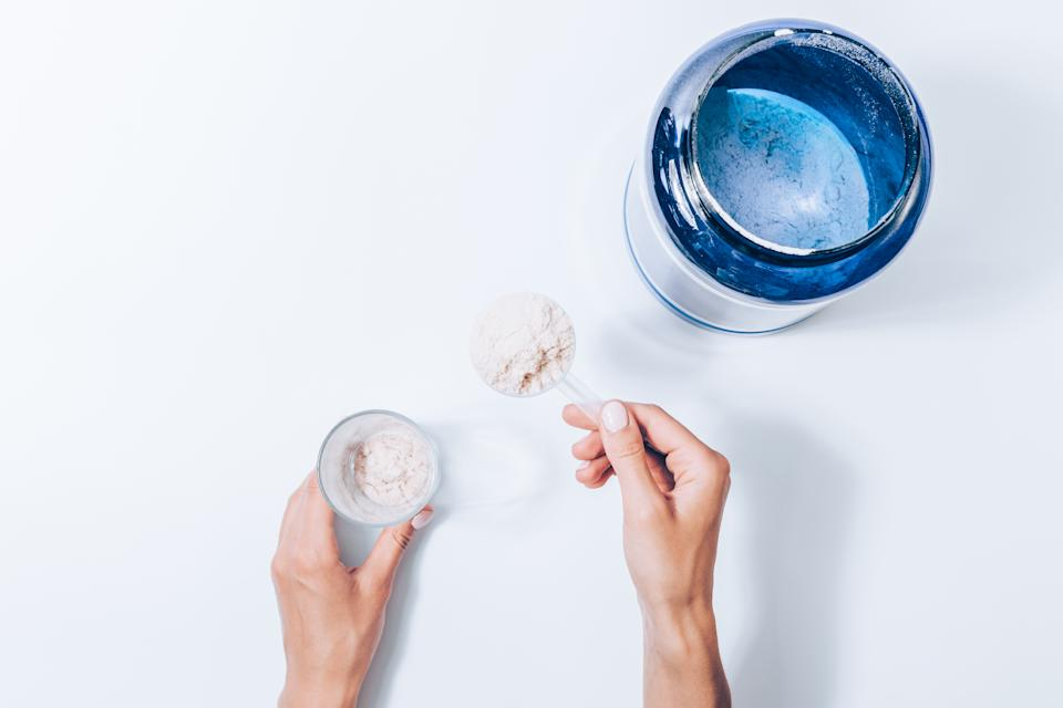 Woman making protein shake, top view. Female hand holding scoop with powder of sports supplements near blue can and gass, flat layout on white background.