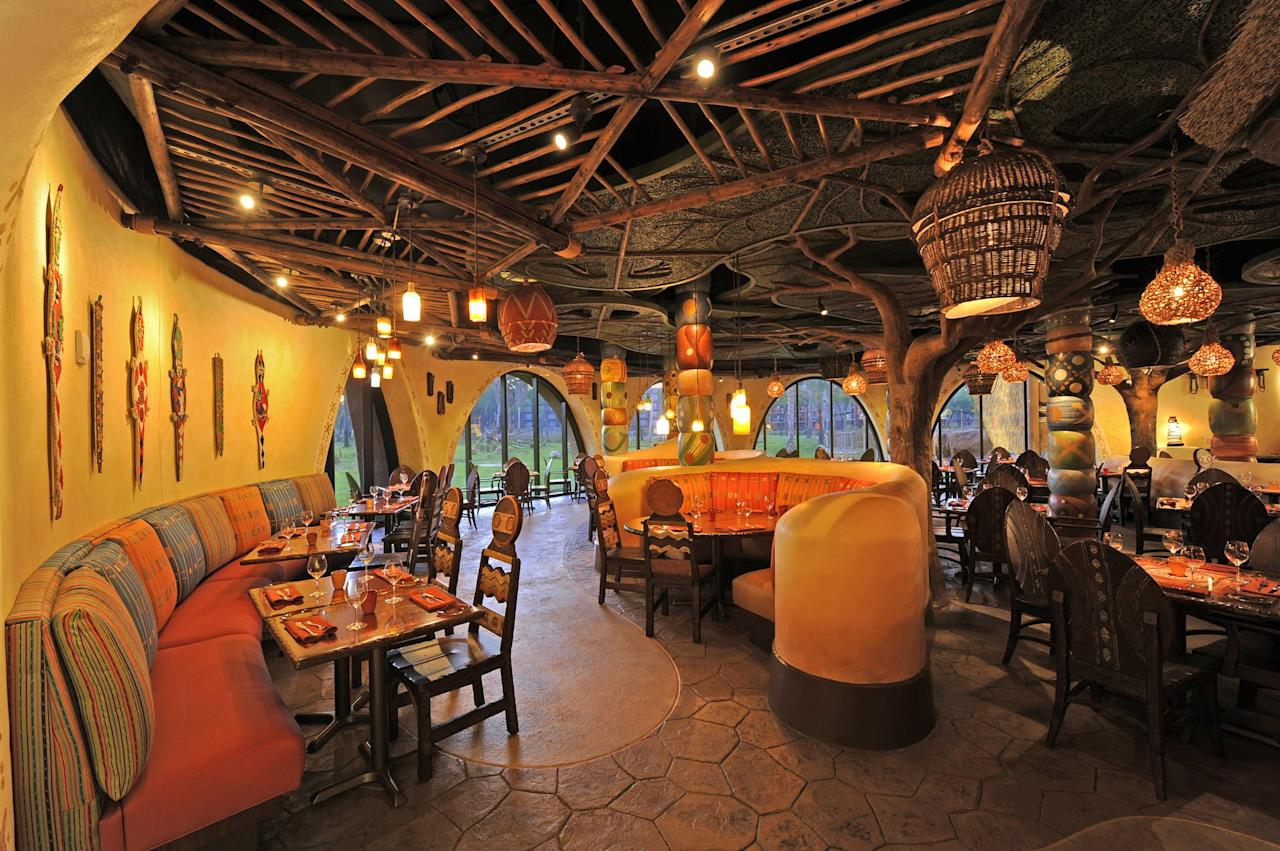 """<p>Your family will have the experience of a lifetime getting dinner at <a href=""""https://disneyworld.disney.go.com/dining/animal-kingdom-villas-kidani/sanaa/"""" target=""""_blank"""" class=""""ga-track"""" data-ga-category=""""Related"""" data-ga-label=""""https://disneyworld.disney.go.com/dining/animal-kingdom-villas-kidani/sanaa/"""" data-ga-action=""""In-Line Links"""">Sanaa at Kindani Village</a>, the <a href=""""https://www.popsugar.com/smart-living/What-Disney-Vacation-Club-44871017"""" class=""""ga-track"""" data-ga-category=""""Related"""" data-ga-label=""""http://www.popsugar.com/smart-living/What-Disney-Vacation-Club-44871017"""" data-ga-action=""""In-Line Links"""">Disney Vacation Club</a> building of Disney's Animal Kingdom Lodge. Even if you're not staying at the resort, you can eat here. A huge perk of eating at Sanaa is watching the animals of the African savanna walk right up to the windows of the restaurant and peer in. For the best view, request a table by the floor to ceiling windows to watch birds, zebra, and other wildlife up close.</p>"""